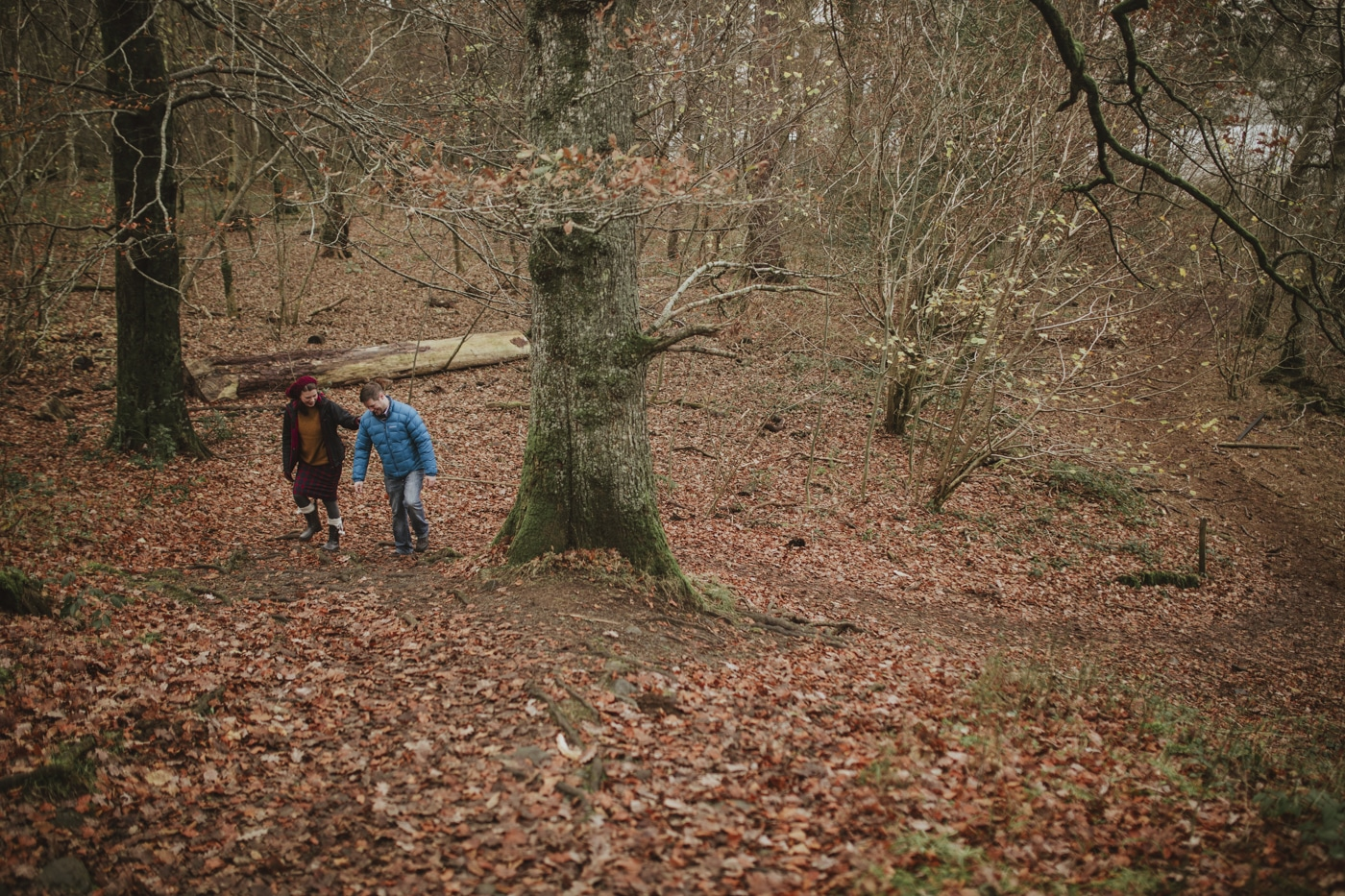 Man and woman walking among trees and leaves in Cumbria by Joshua Wyborn Photographic