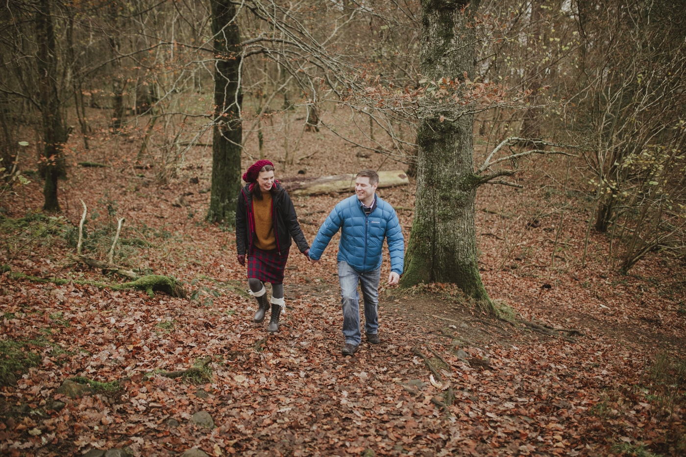 Man and woman couple portrait walking up leaf covered hill in forest in Cumbria