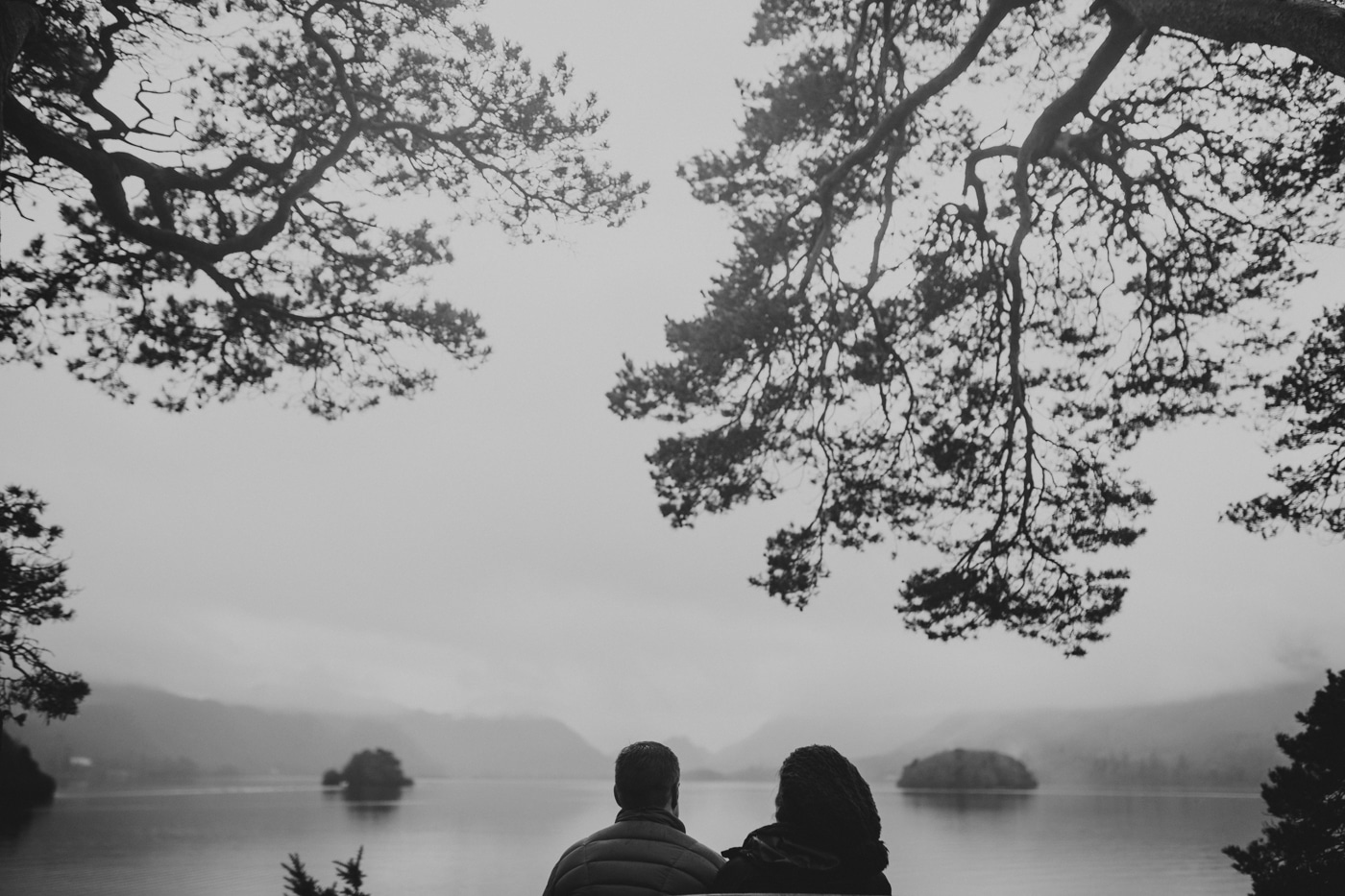 Couple looking out on a misty lake by Joshua Wyborn photographic Cumbria Photographer