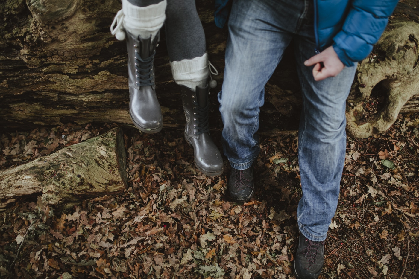 Couple in boots and wellies sitting on a log by Joshua Wyborn Photography