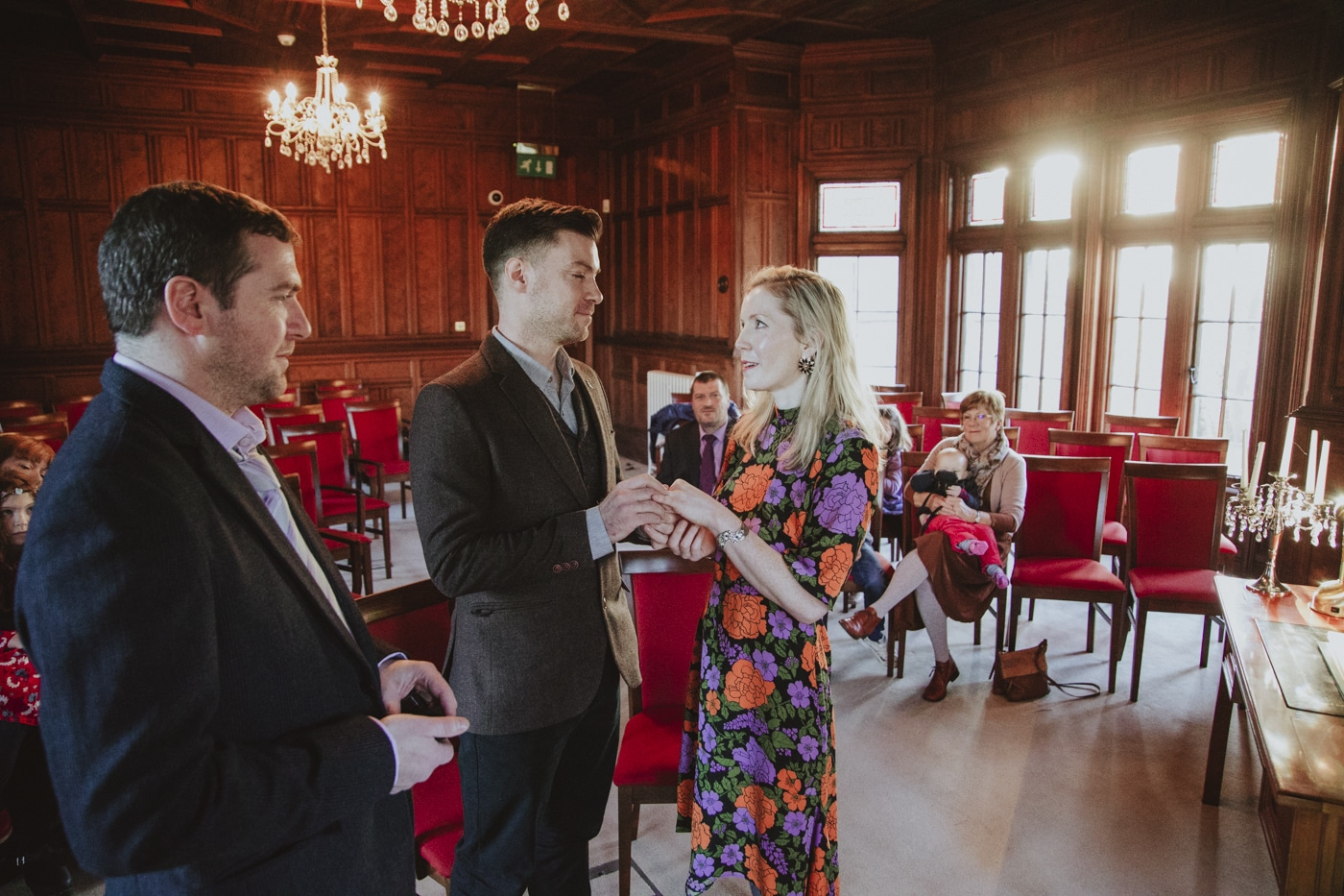 Man and wife during wedding in wooden panelled red room by Joshua Wyborn Photographic