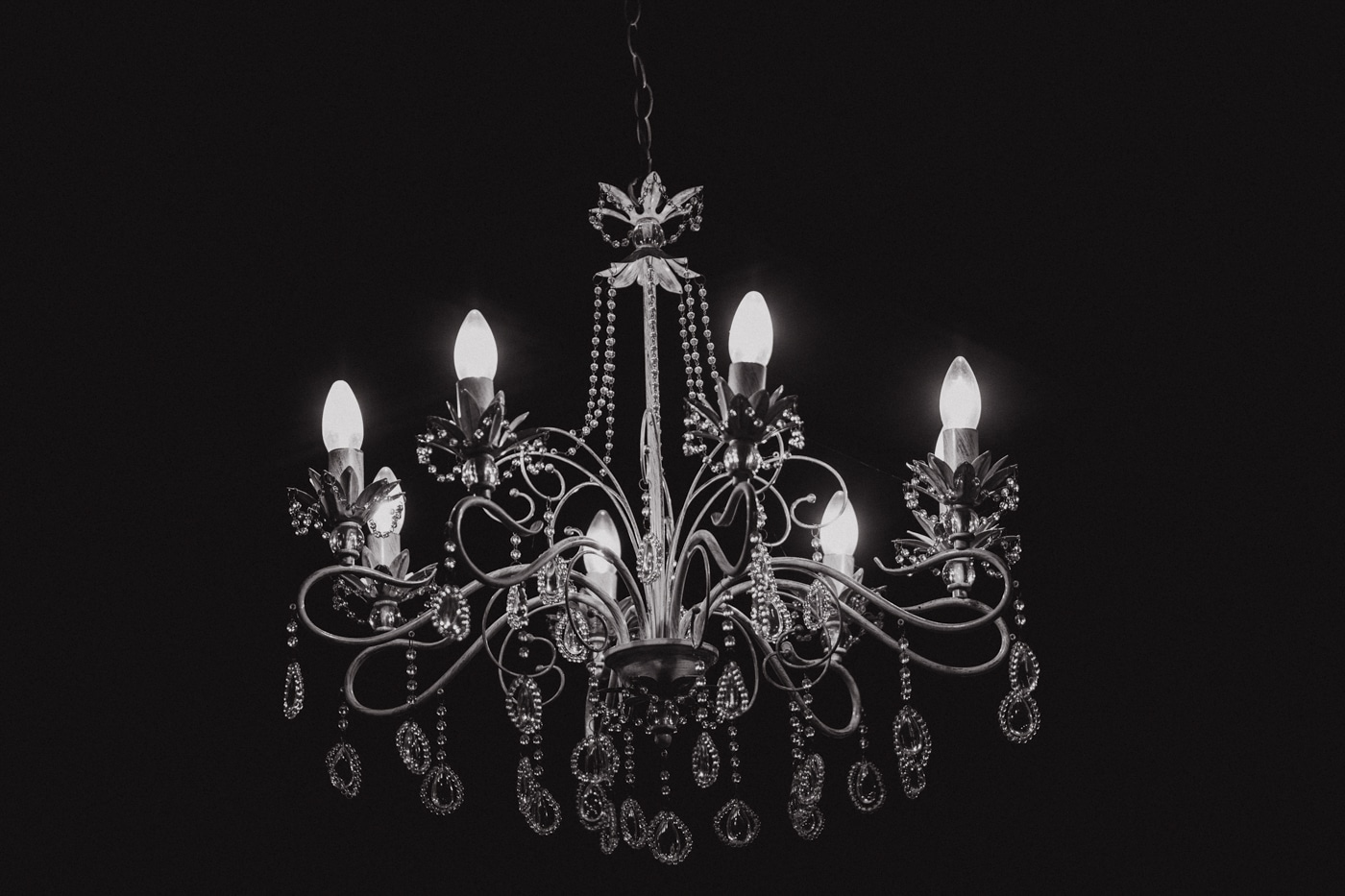 Chandelier with lights in the dark by Josh Wyborn