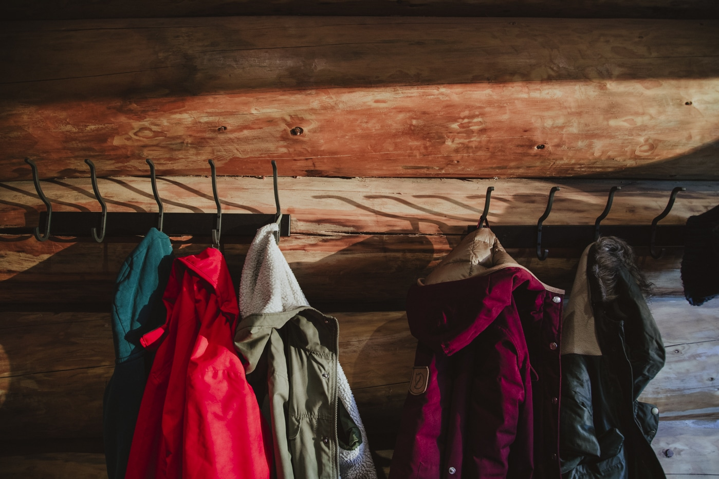 Coats hanging on a wooden hooks by Joshua Wyborn