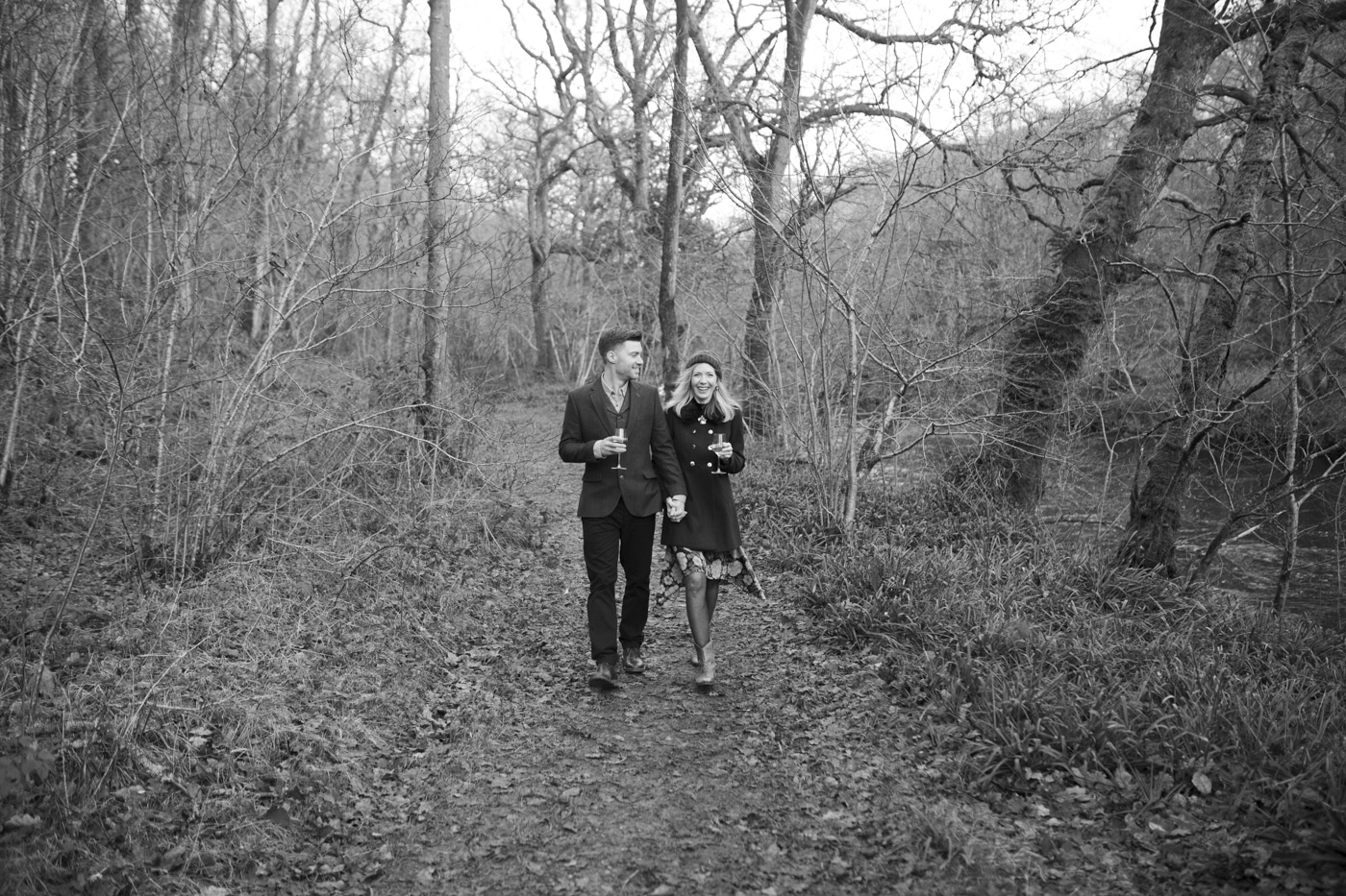 Man and woman walking through woodland with drinks by Joshua Wyborn Photographic