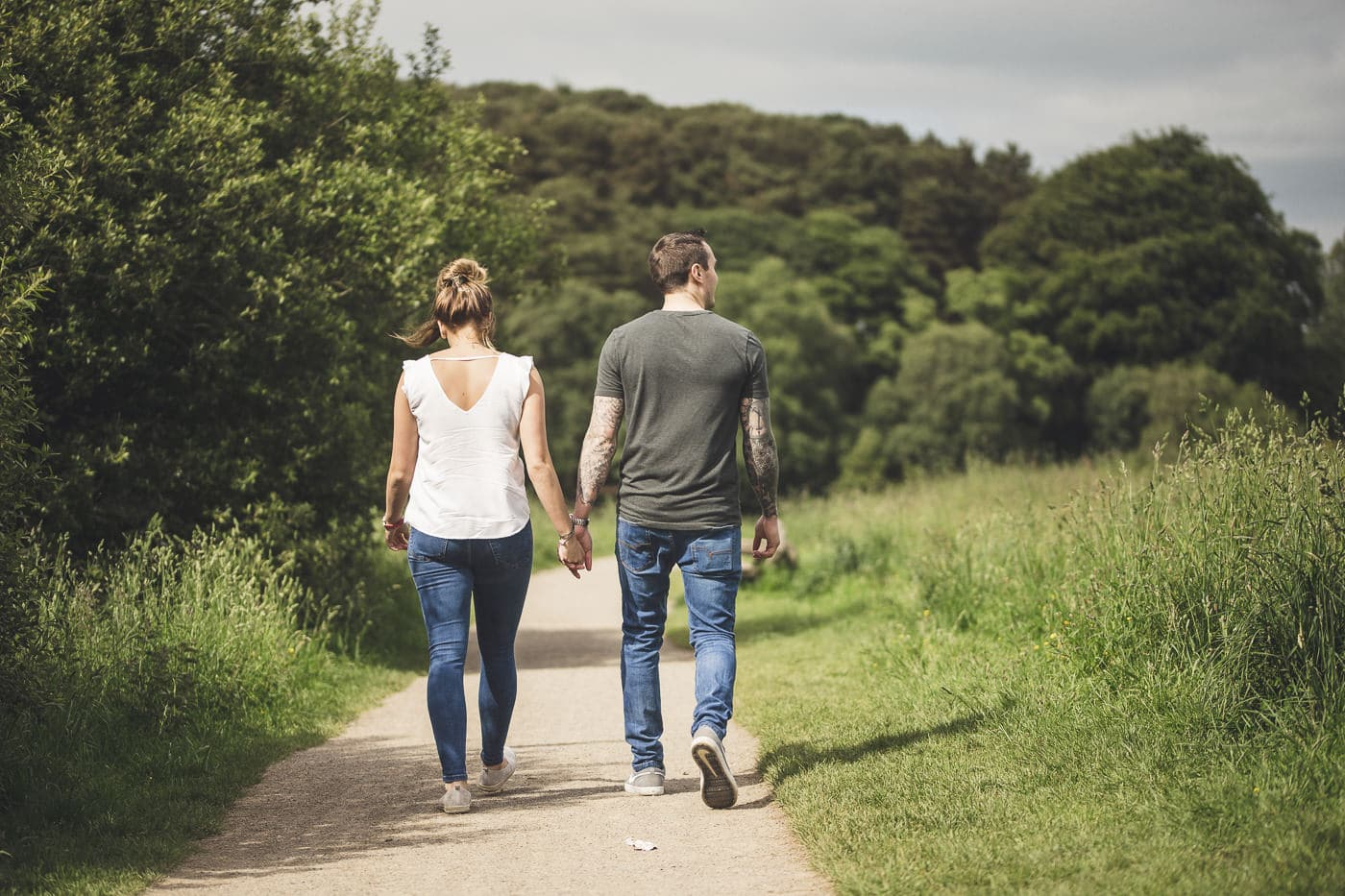 Couple walking down a path in cumbria along side the lake side