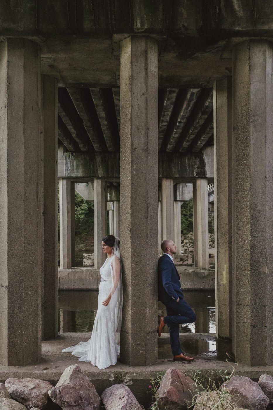 Bride and Groom on their wedding day resting against pillars under a bridge in a creative wedding photograph