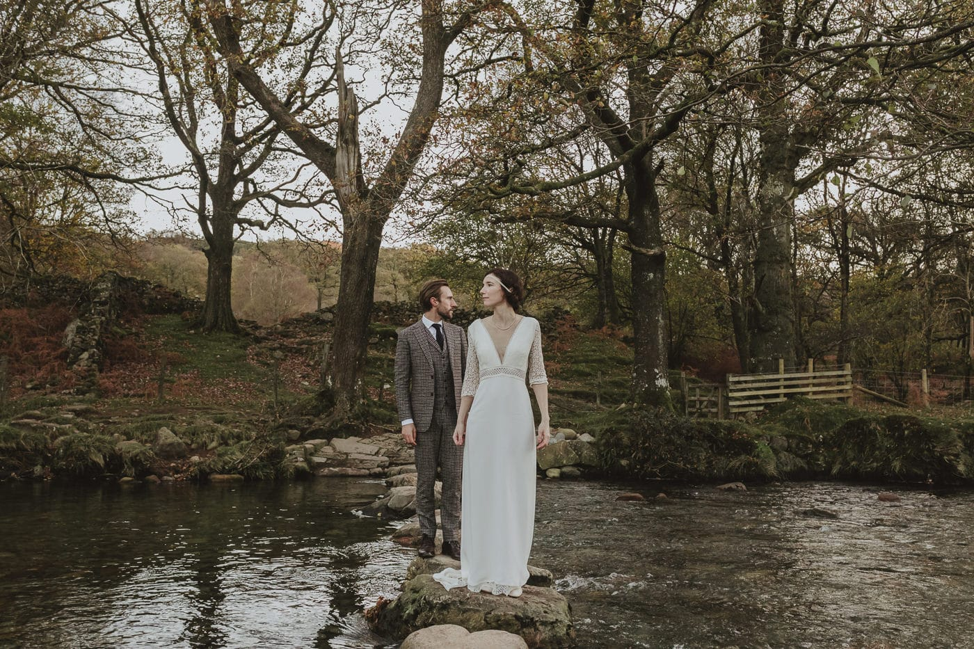 Bride and groom standing over a Cumbrian river in the Eskdale valley