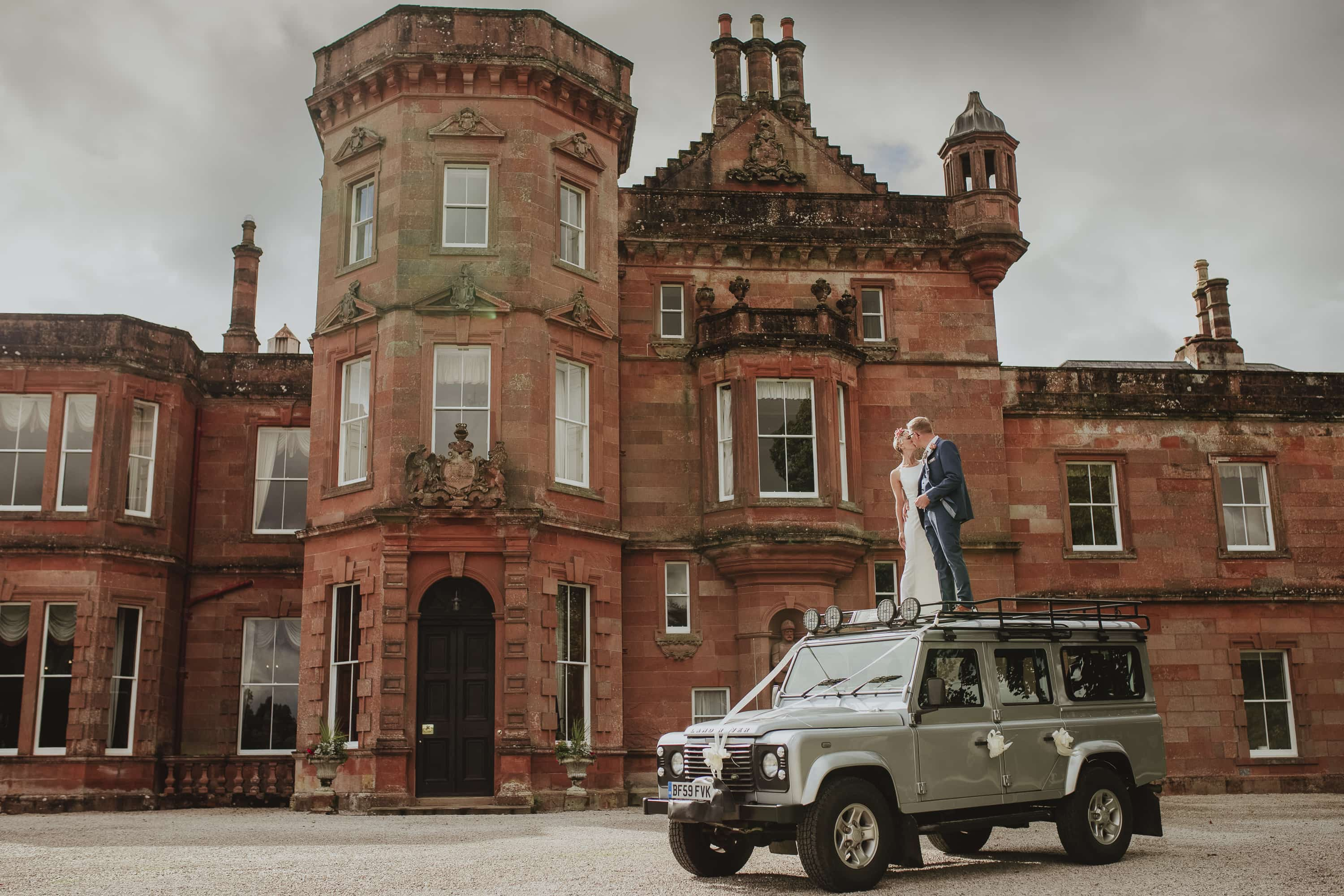 Bride and Groom stood on top of a landrover in Cumbria