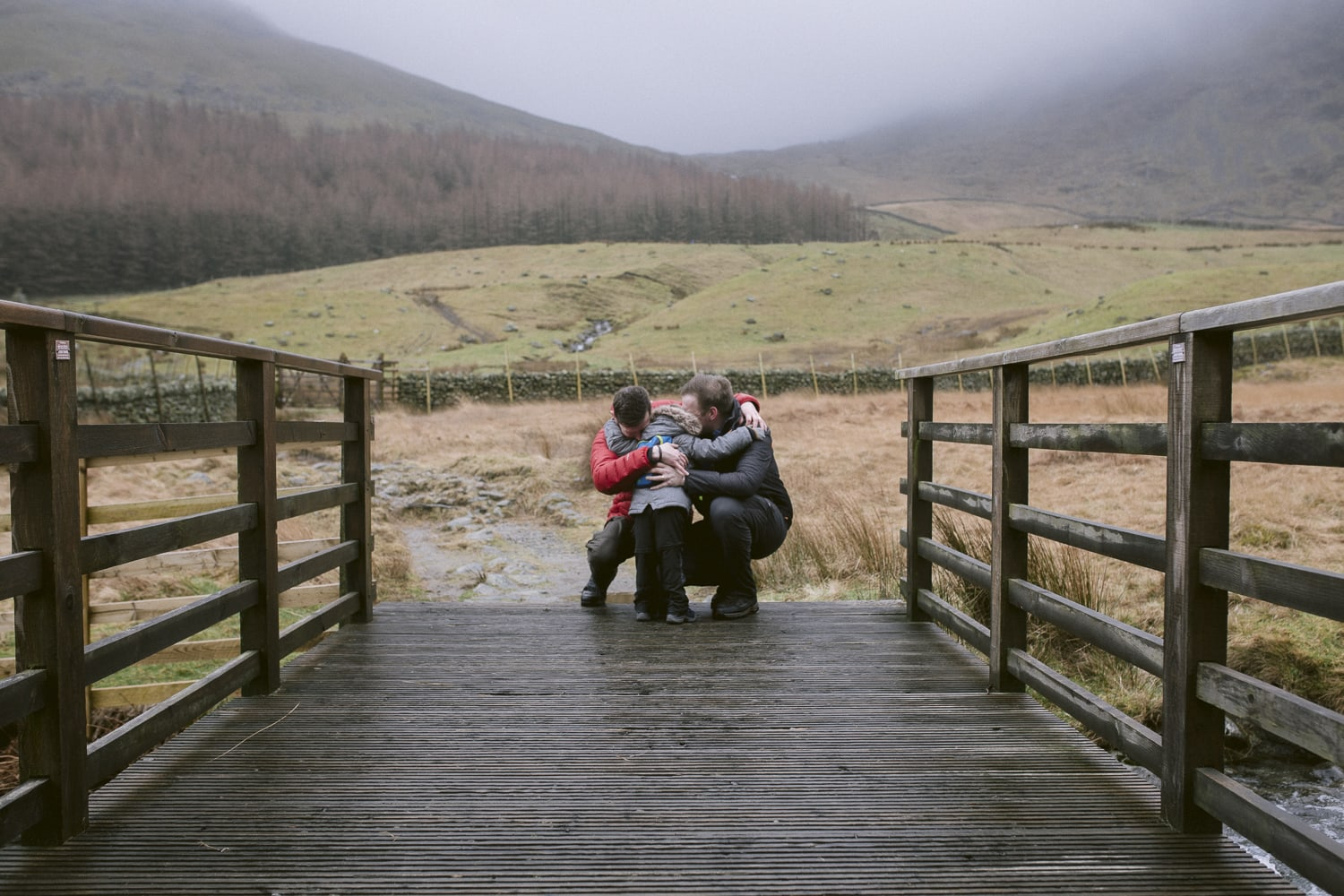 two fathers hugging their son on a lake district photoshoot