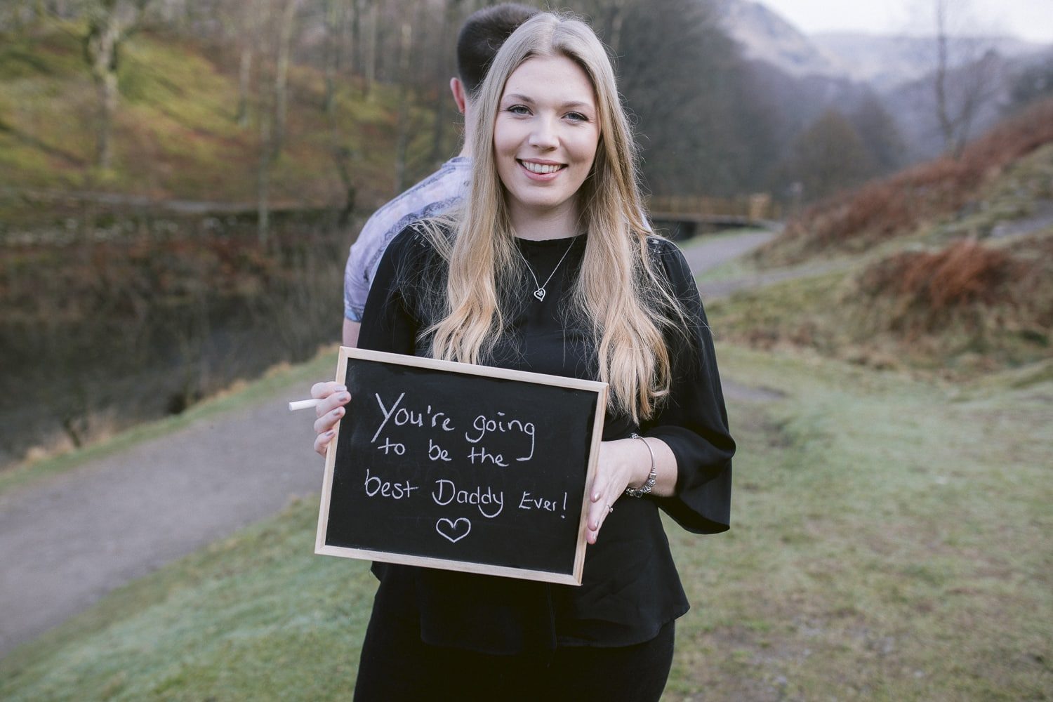 Wife to be holding baby announcement black board