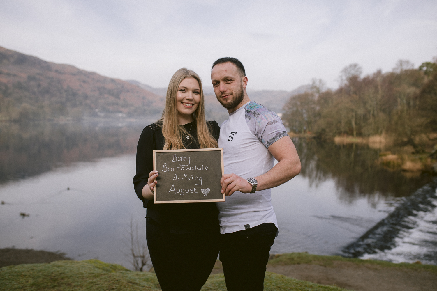 Baby announcement photo couple holding blackboard.