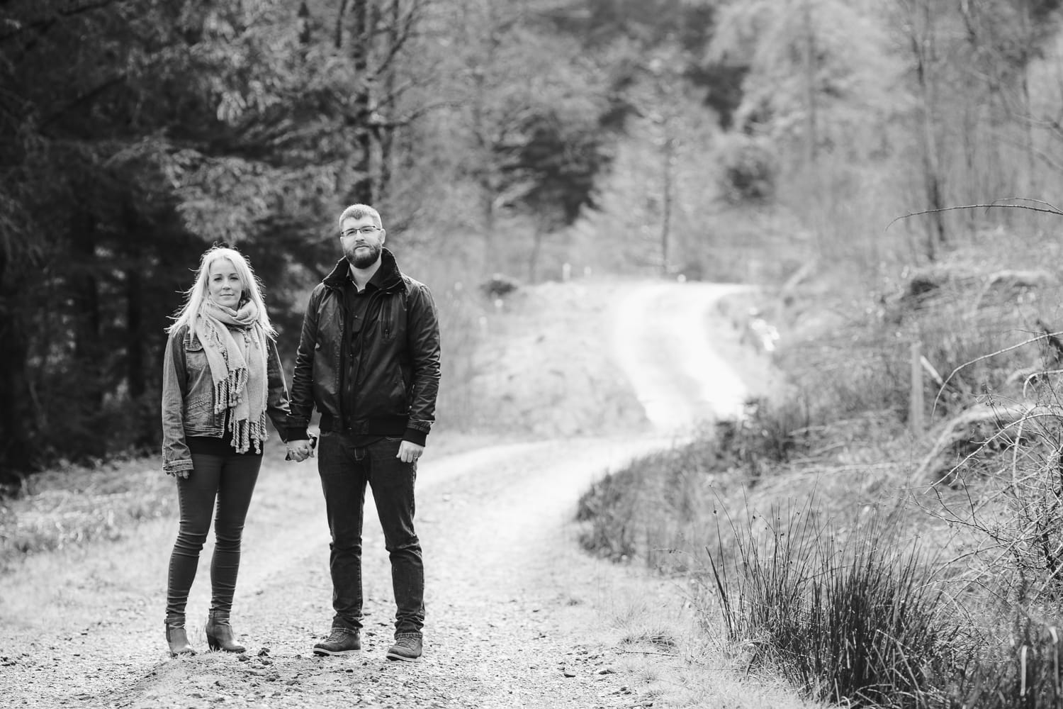 couple holding hands on a country path at whinlatter forest
