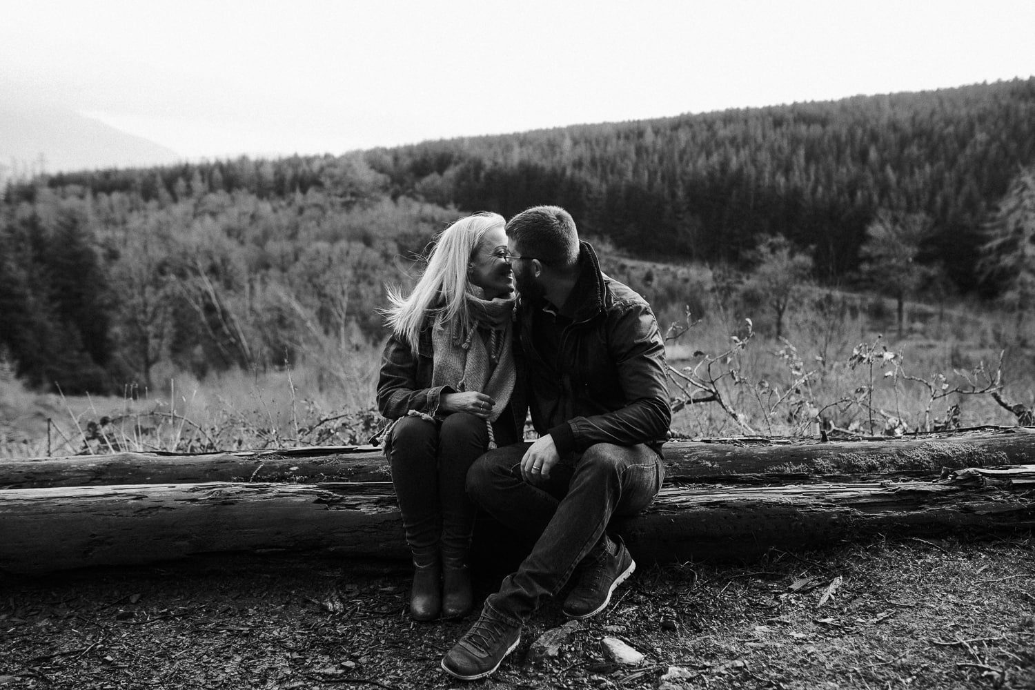 Couple sat on a log at whinlatter forest in the lake district
