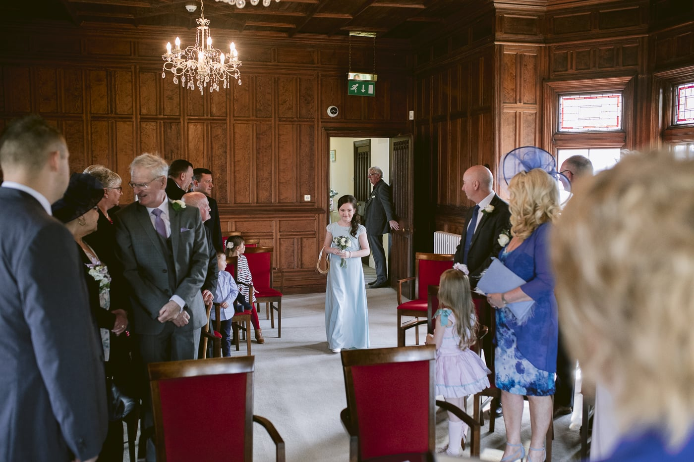 Brides maid walking down the aisle at guests at Carlisle Registry office