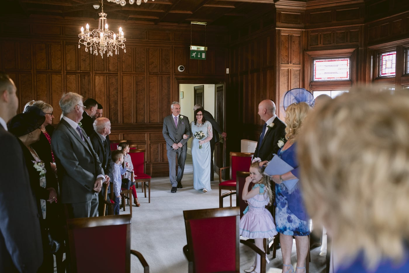 bride and father walking down aisle at guests at Carlisle Registry office