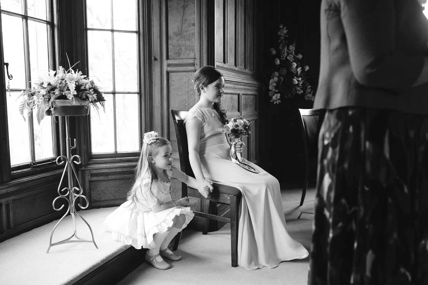 bridesmaid and child sat down in ceremony.