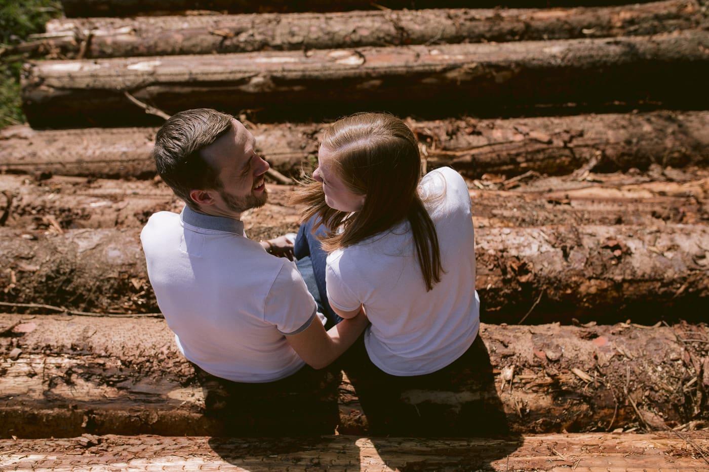 Couple Sitting On Logs Portrait Session