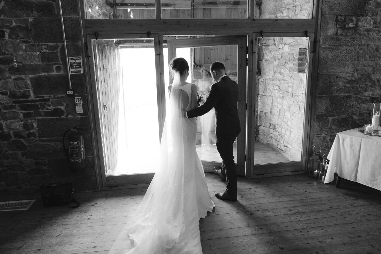 Beth and Ryan Walking Through Wedding Hall Doors