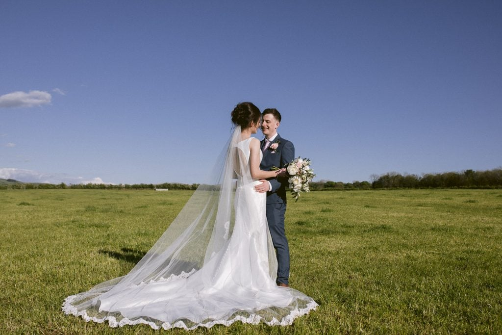 Bride and groom stood for a photograph at Three Hills Barn Field