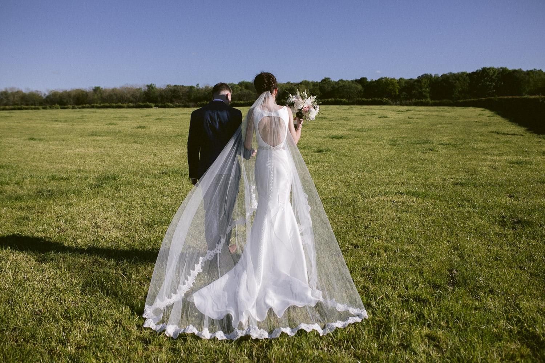 Long Bride Wedding Dress and Groom Walking in a Field, Sunshine Portrait Shooting