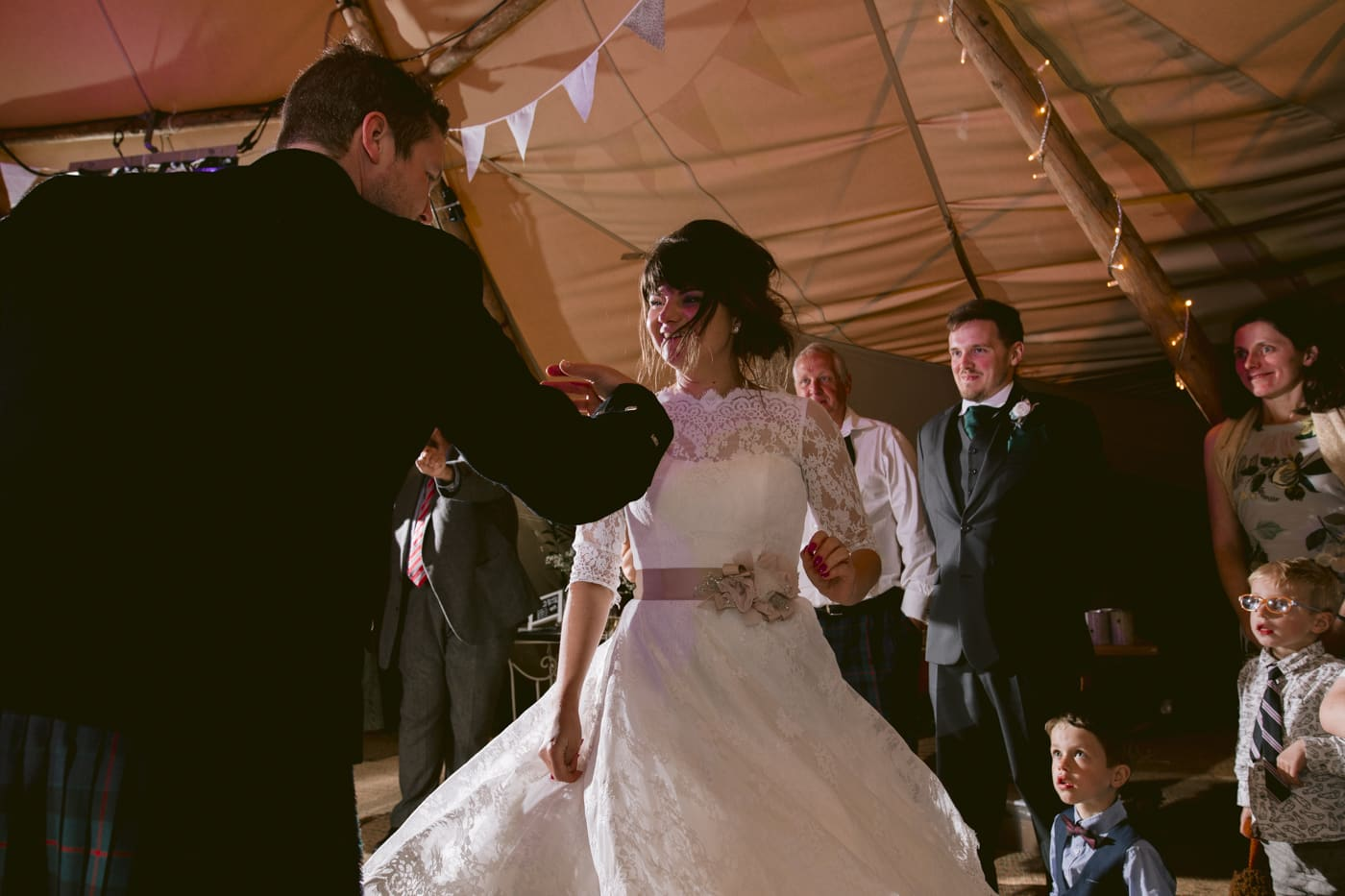 Dancing Bride with Groom Taking Lead Under Tipi Tent