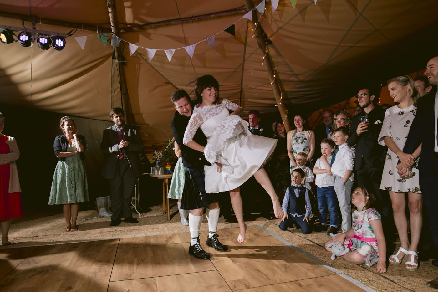 Bride and Groom Twist and Dance Under Tipi Tent in Lake Destrict