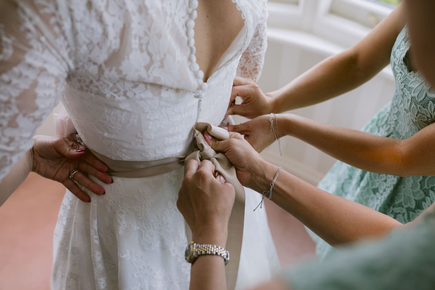 Zipping up the Wedding Dress with Bridesmaids Photograph