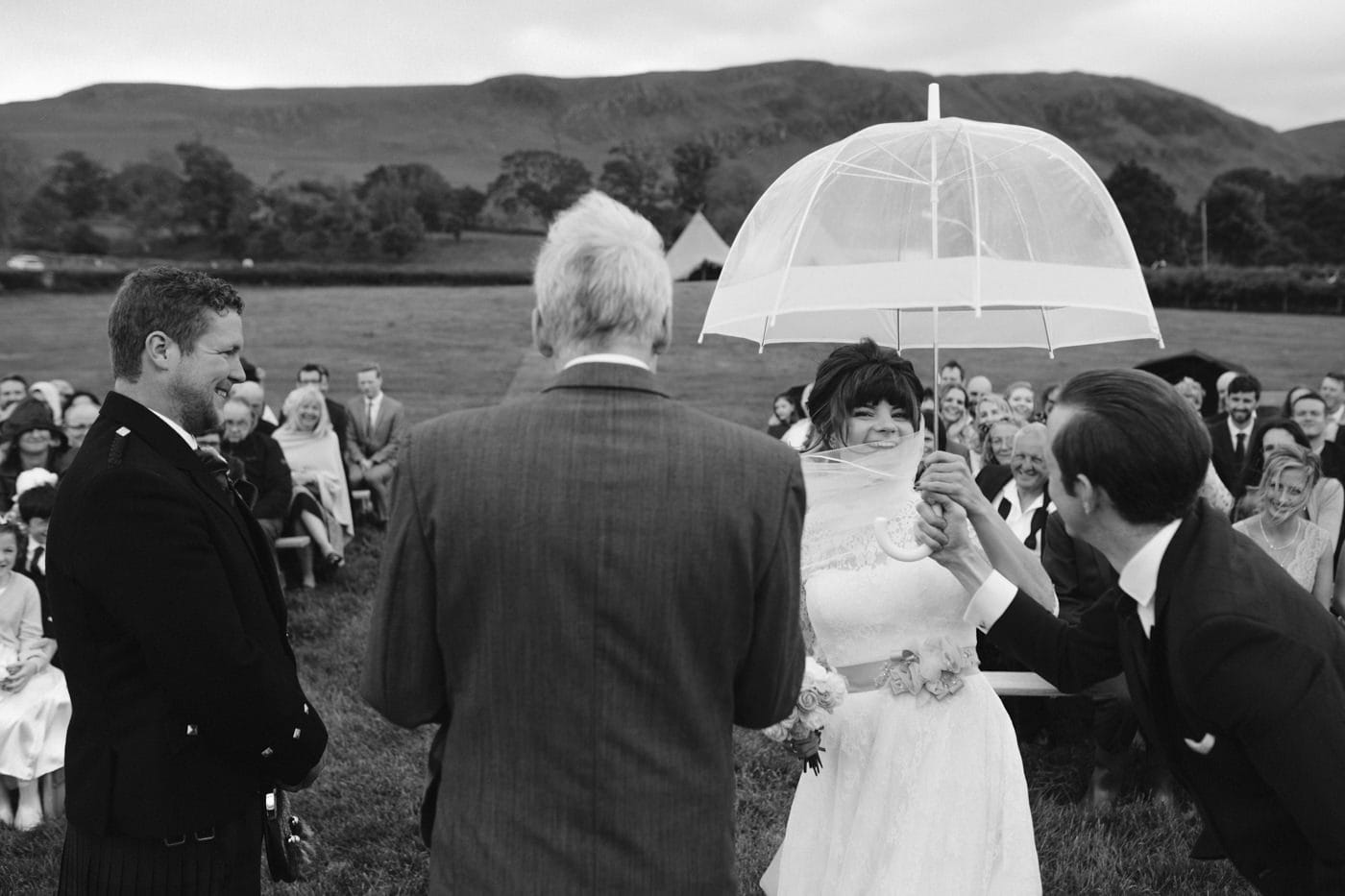 Minister Taking Ceremony with Bride and Groom at Tipi Wedding On The Shores Of Ullswater