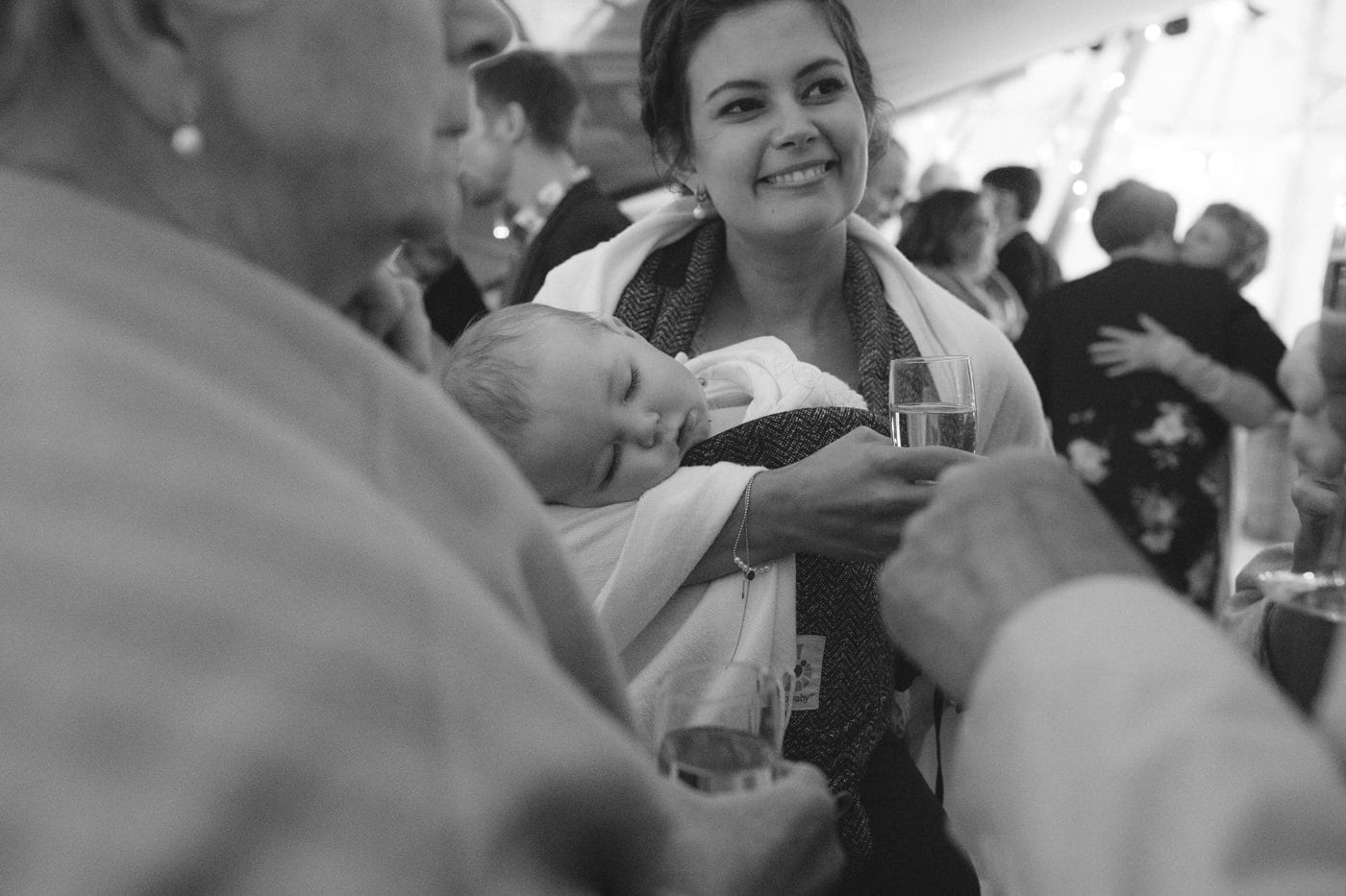 Guests Smiling and Baby Sleeping in Main Venue at Tipi Wedding On The Shores Of Ullswater