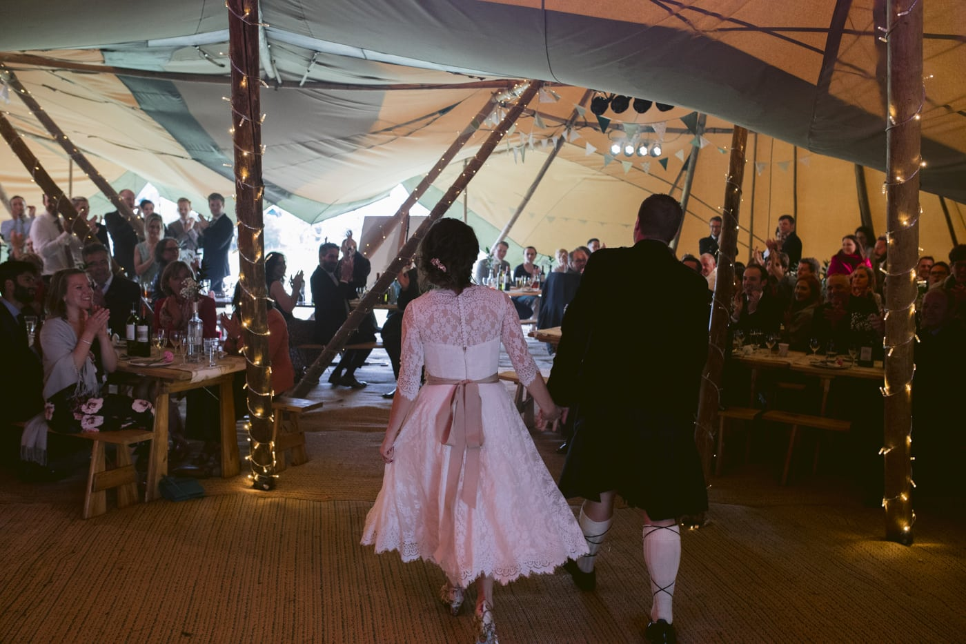 Bride and Groom Walking in Tipi Tent towards Guests