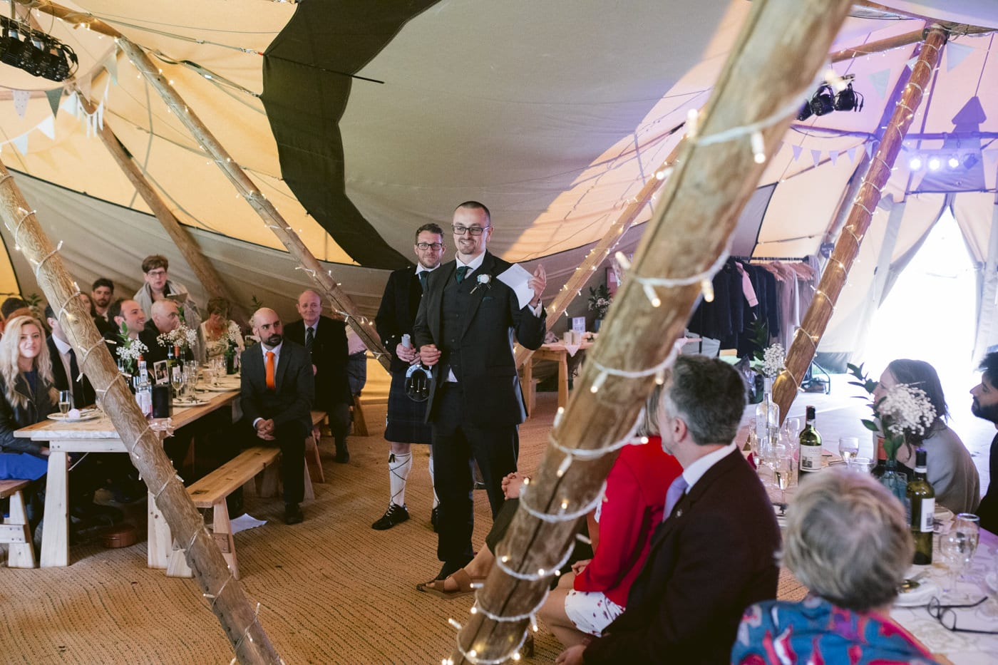 Guests Seated on Bentches in Tipi Tent