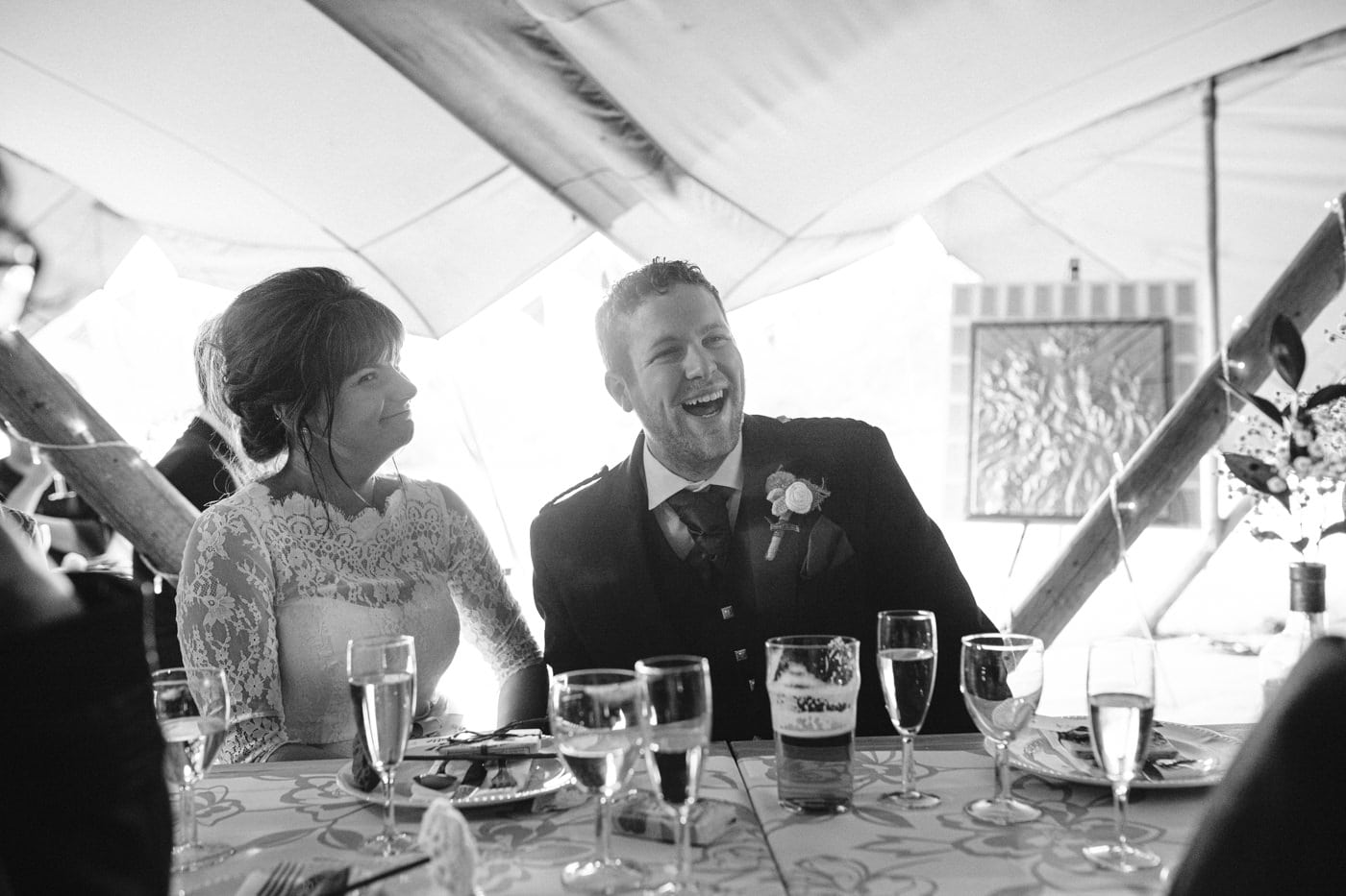 Bride and Groom at Tipi Tent Table Filled with Wine and Food