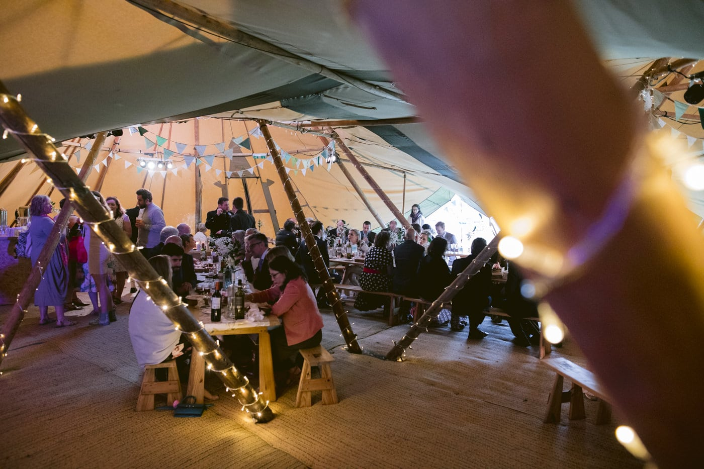 Evening Tipi Lights and Guests Sitting Down