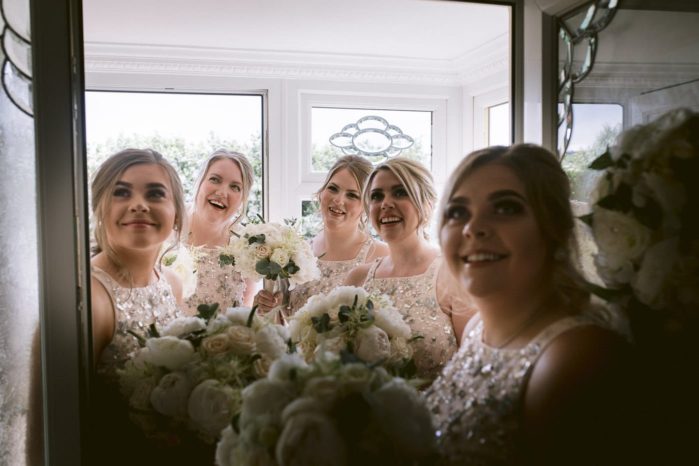 Smiling Photography of Wedding Day Bridesmaids and Arranged Flowers