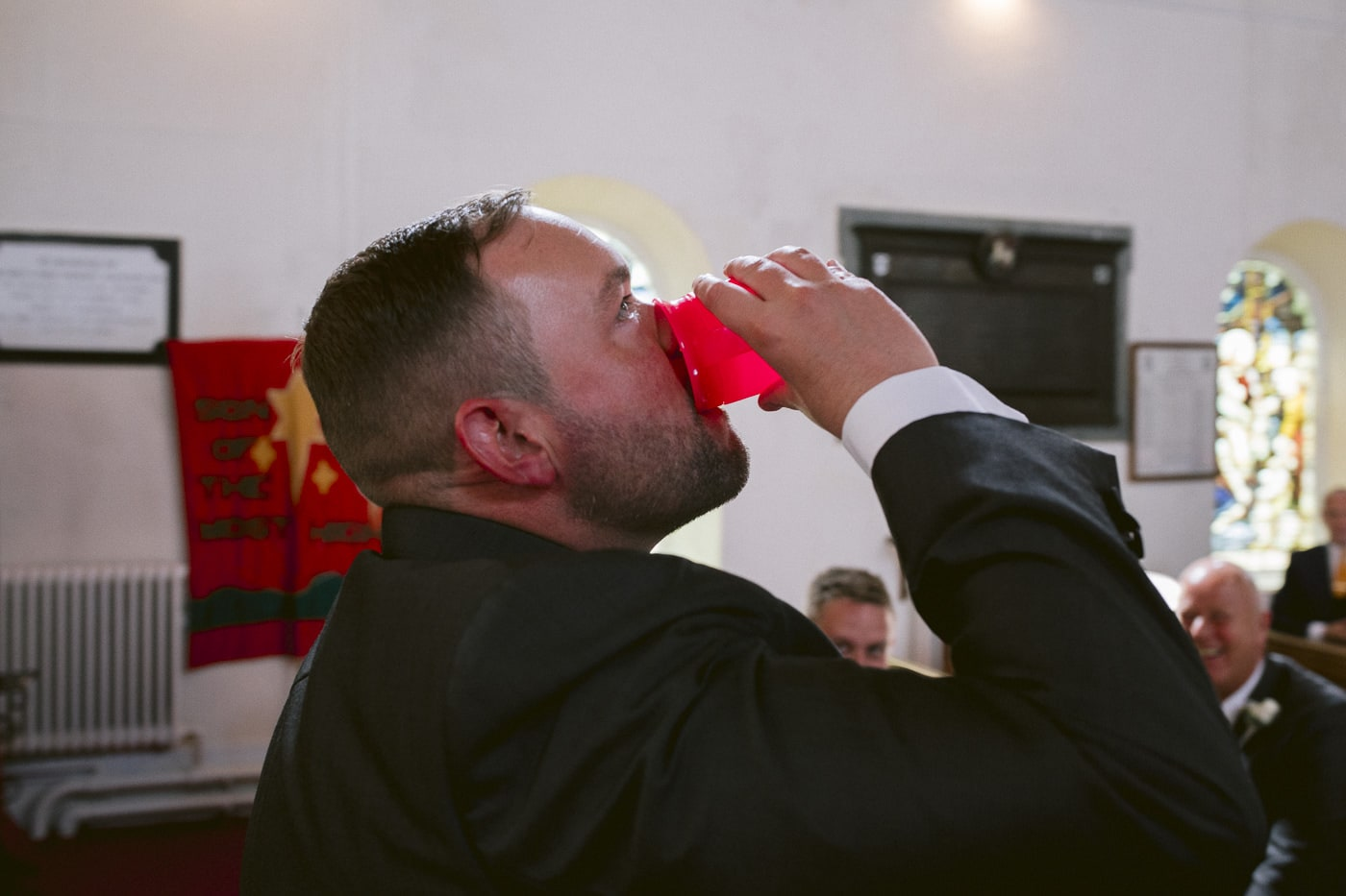 Photograph of Man Drinking From a Red Cup