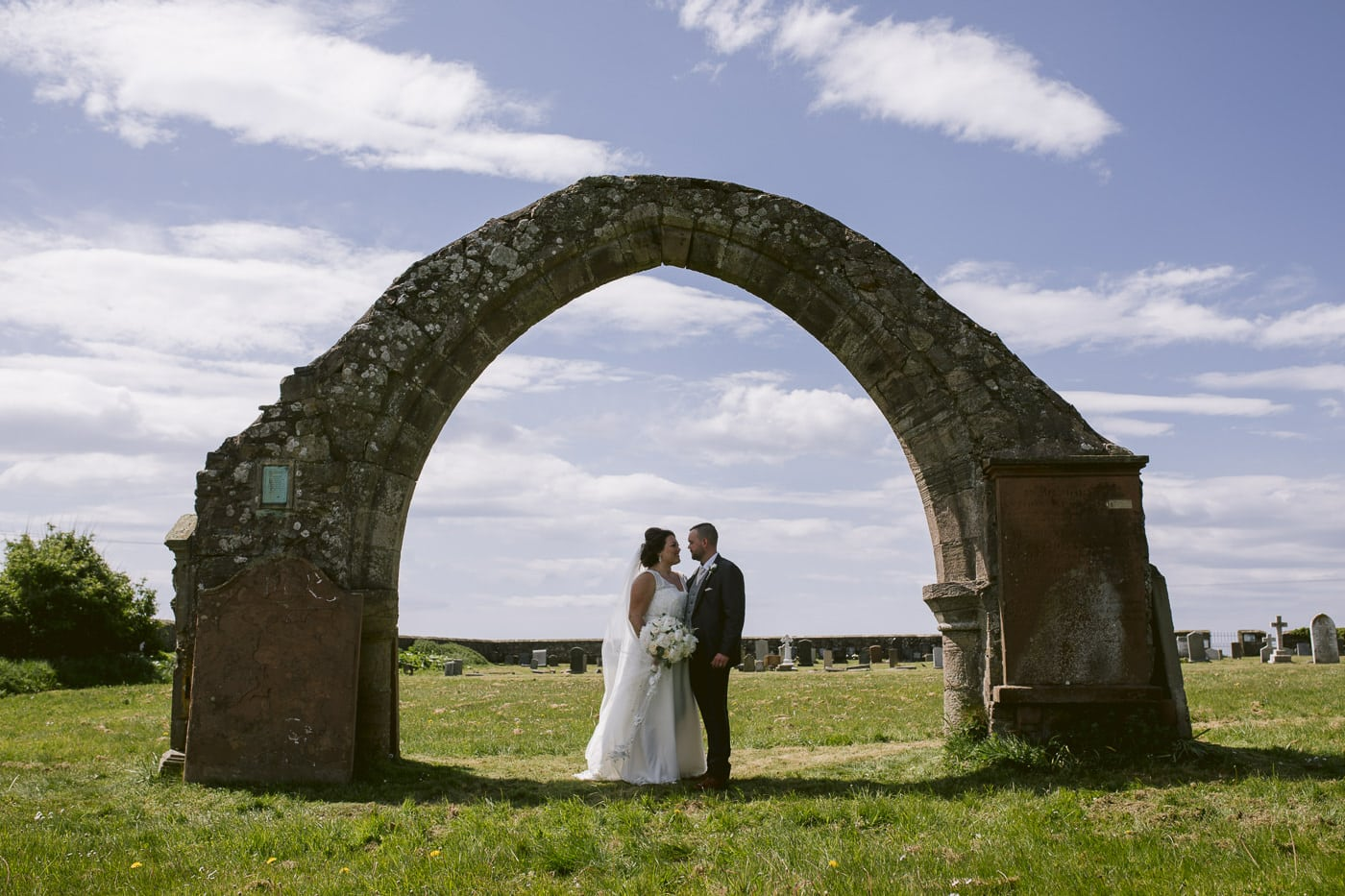 Bride and Groom Under Archway, Sunny Background Wedding Photography Session