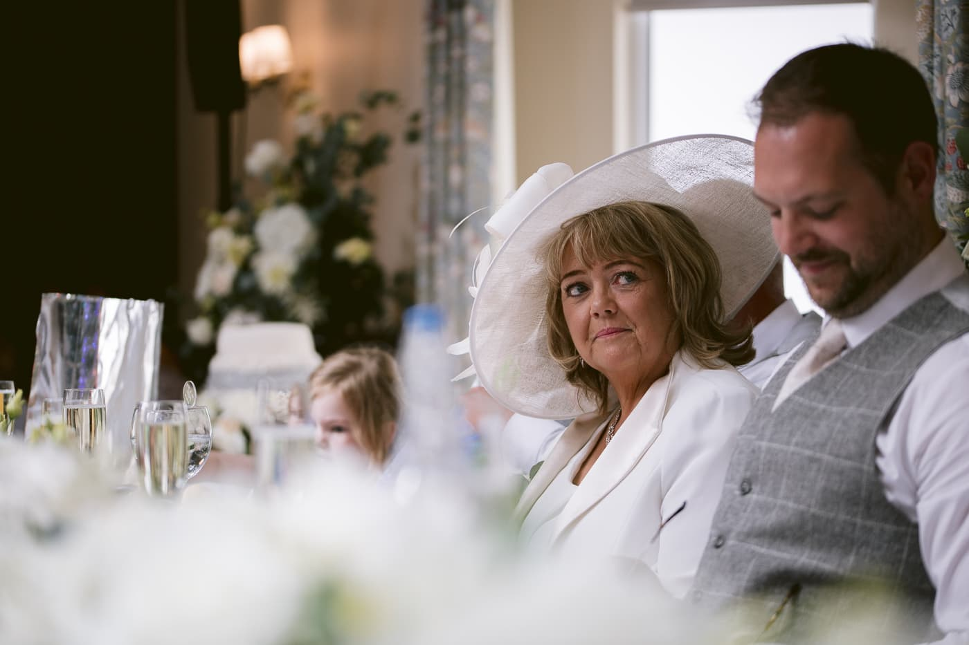 Woman in Big Wedding Hat Looking Forward With Guests in Reception Main Hall Photo Shoot Session