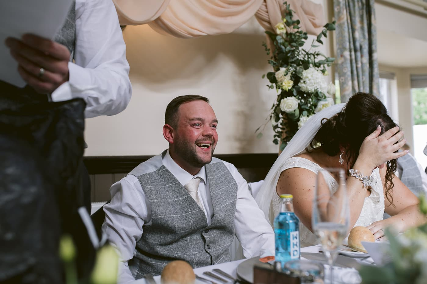 Groom Sitting at Table Laughing Photography Shoot