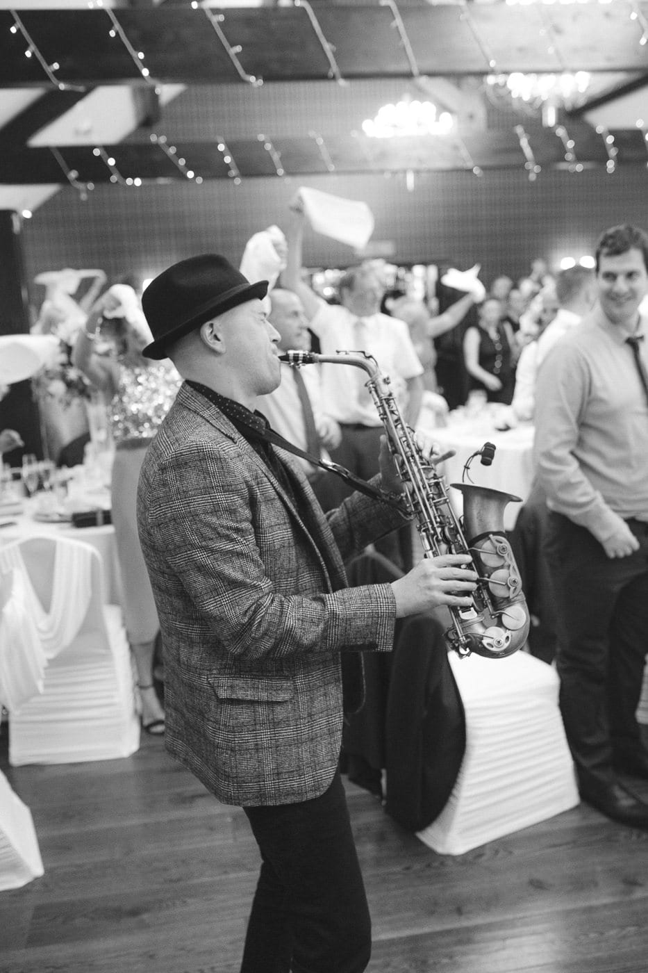 Man and Checked Top and Hat Playing Saxophone at Reception Room Photography