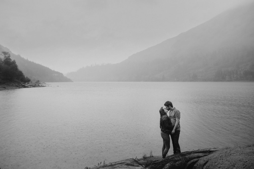 Couple Photograph standing in the rain at a lake edge kissing