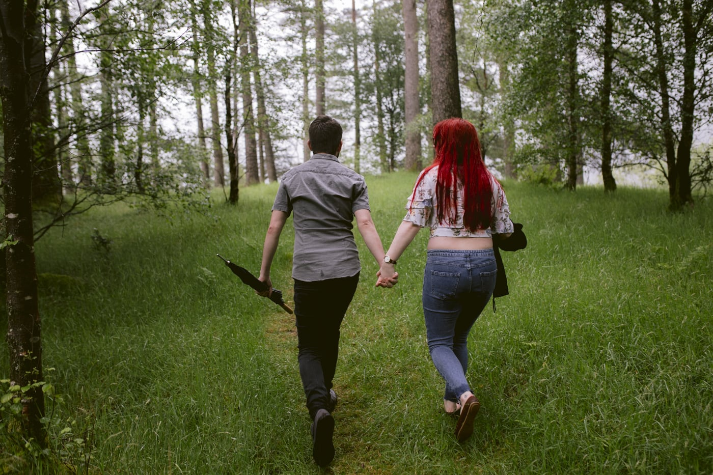 Couple Hand in Hand Walking on Grass in Forest Portrait Session