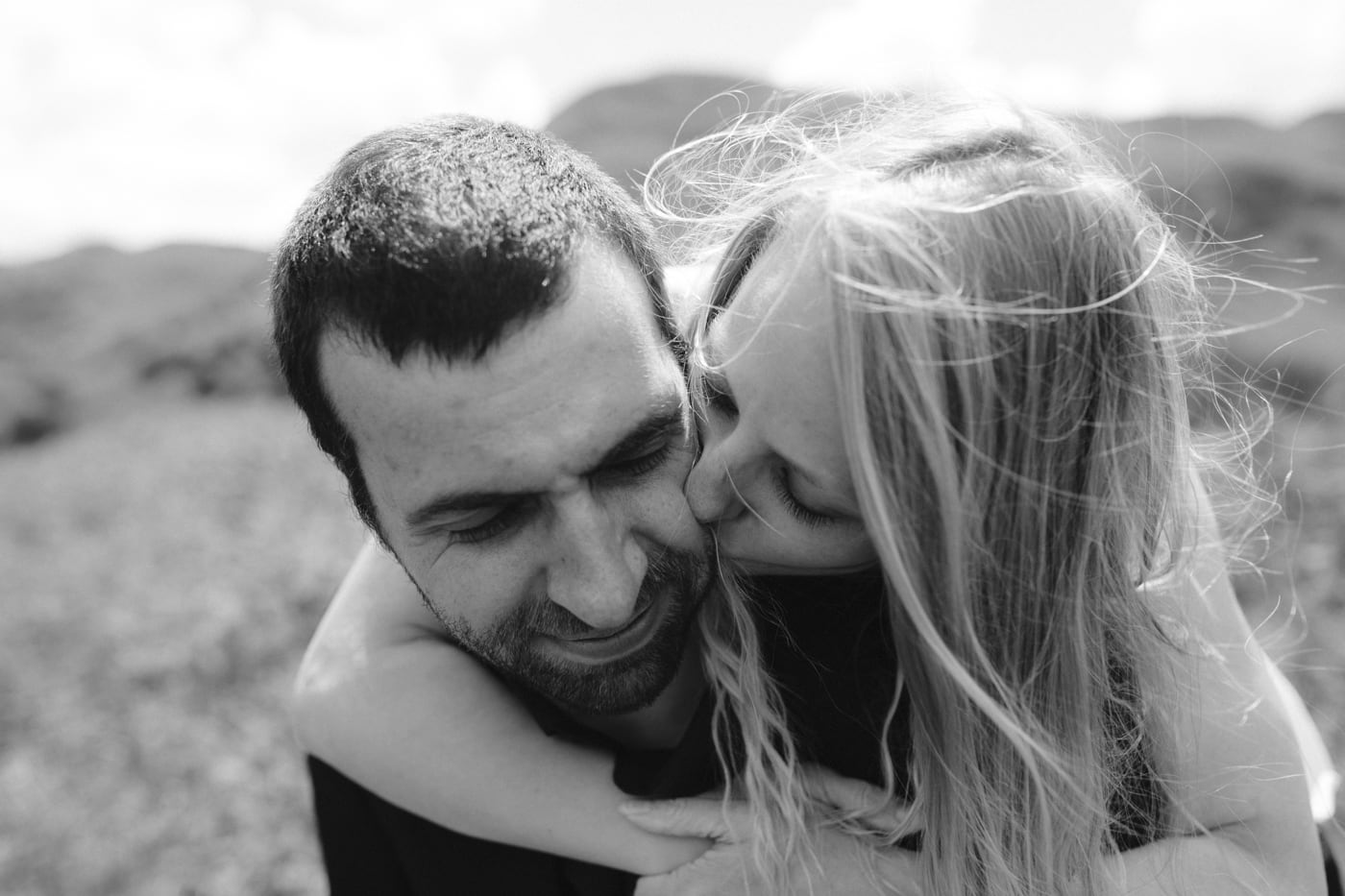 Bride on Grooms back Kissing Cheek in the Open Air Portrait Session