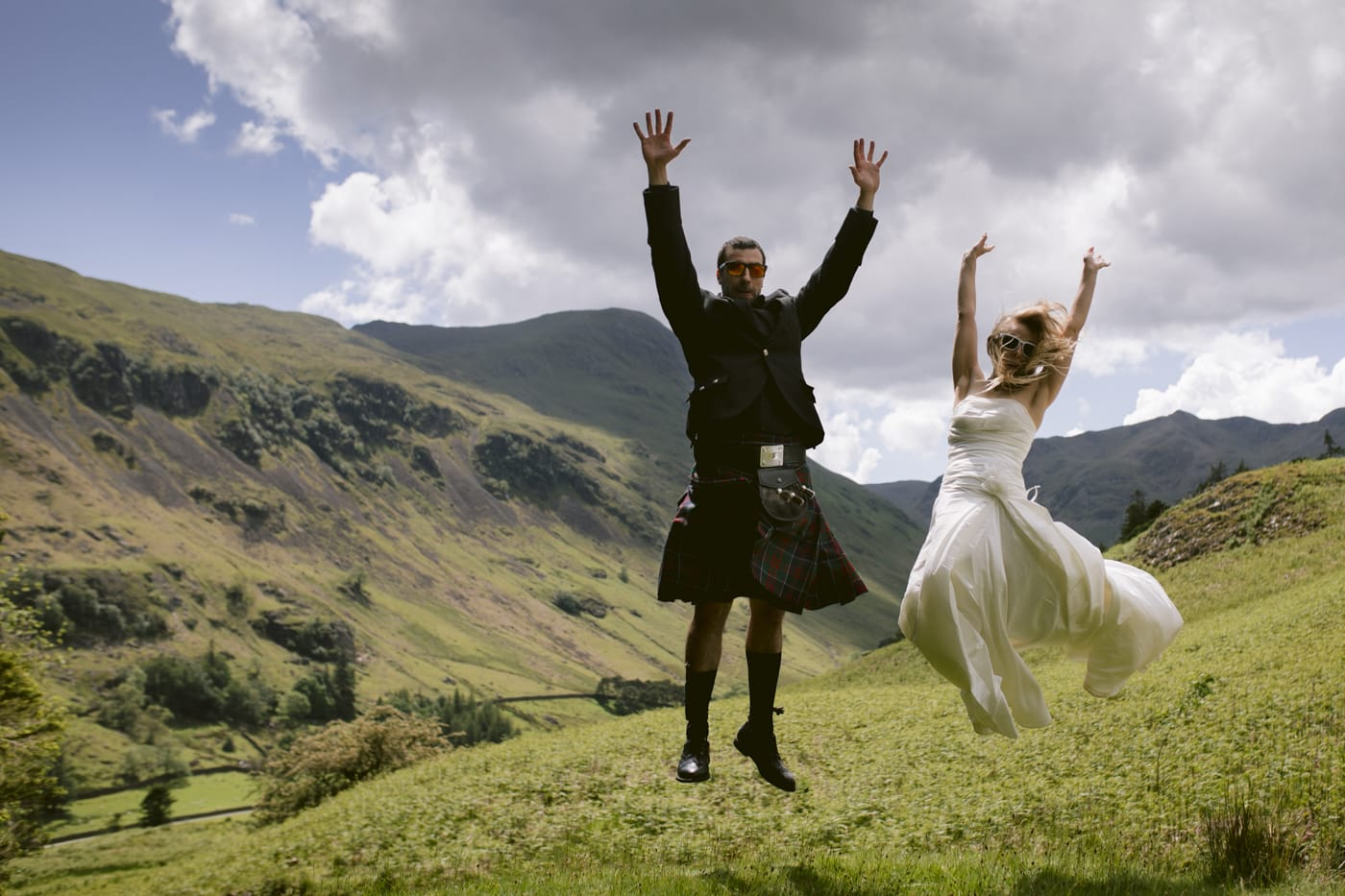 Bride and groom jumping in the air in the lake district on their tenth wedding anniversary