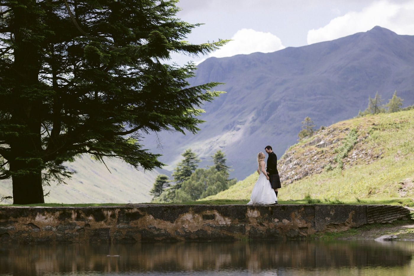 Bride and Groom walking back across the Lake Portrait Session