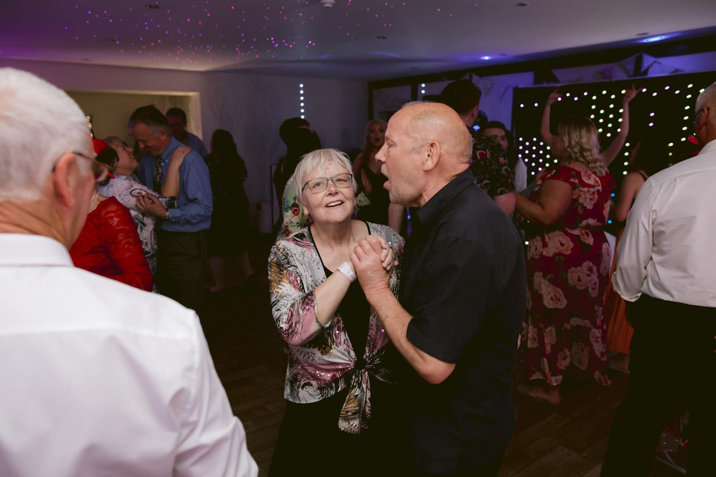 Older Couple Dancing with Guests Portrait
