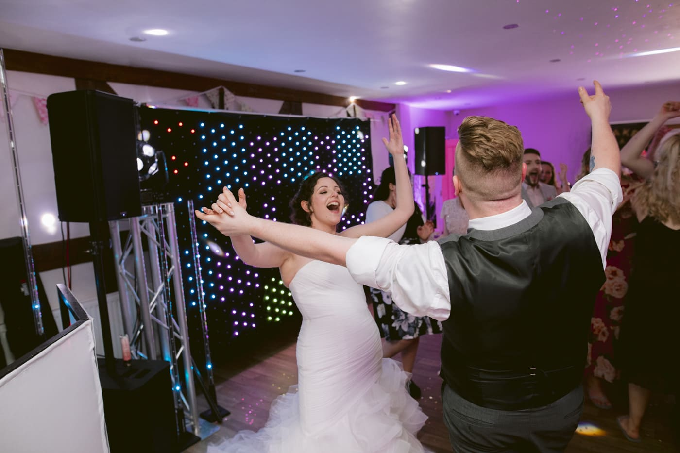 Bride and Groom Reaching Arms on Dance Floor Portrait