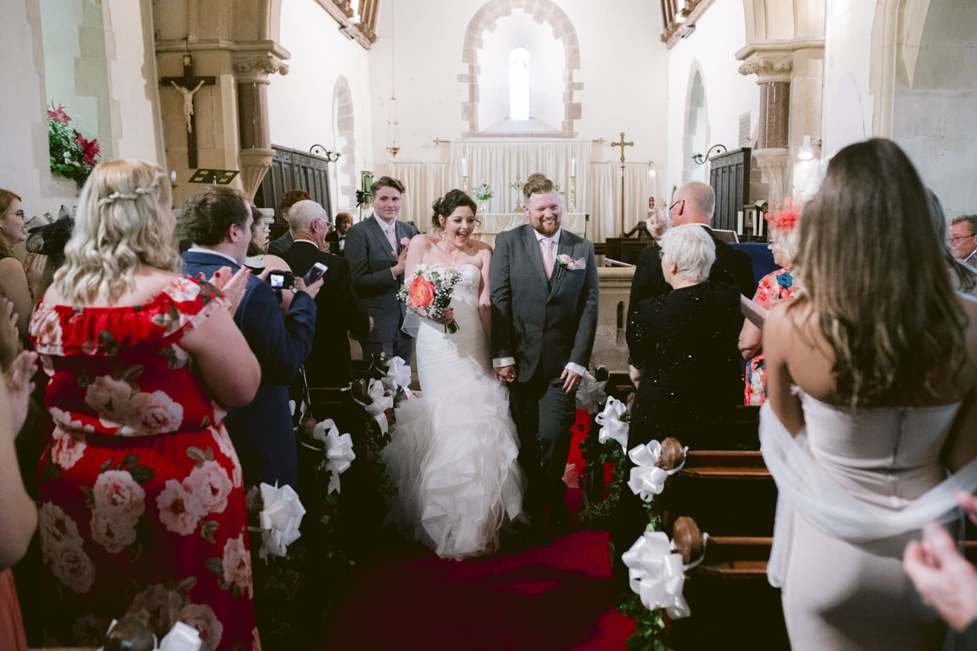 Bride and Groom Walking Down the Aisle Together in Church Main Hall Portrait