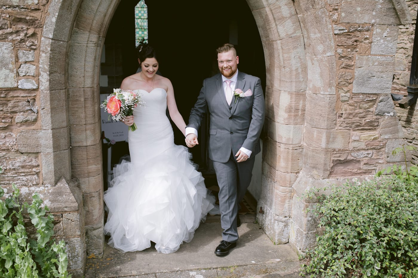 Bride and Groom Walking under the Church Archway Portrait Photography