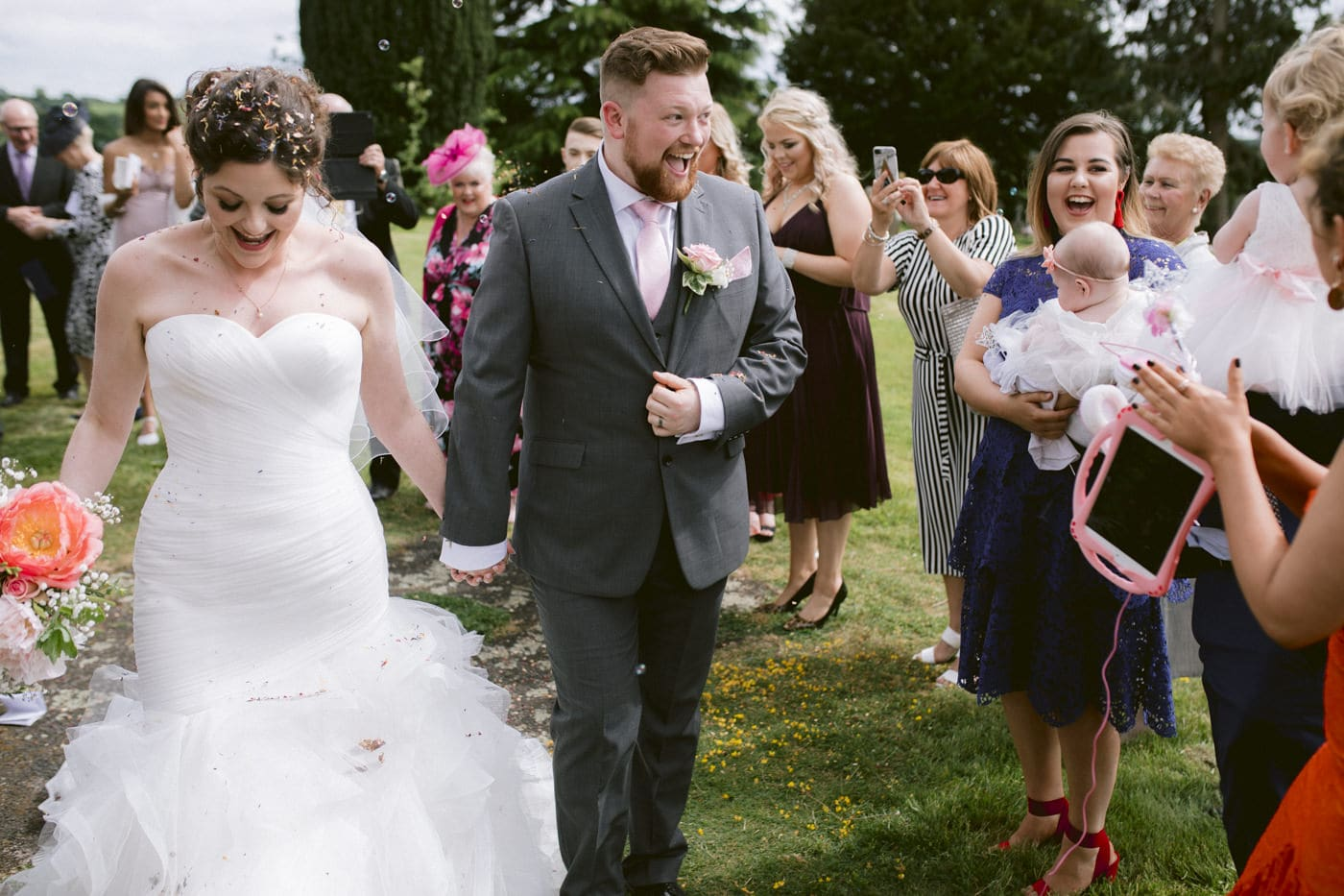 Guests and Bride and Groom Laughing, Celebrating outside while Walking Portrait Photography