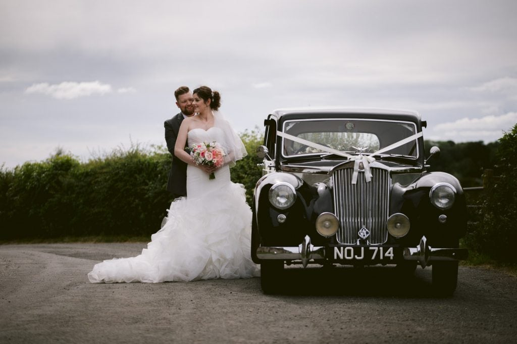 Bride and groom next to wedding car